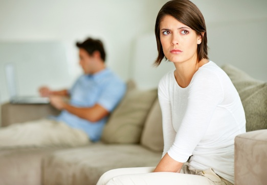 Portrait of a upset young female looking away while her husband using laptop in background